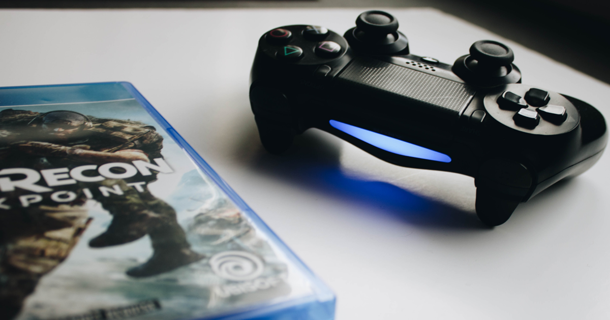 A photograph of a copy of Ghost Recon, alongside a PlayStation 4 controller