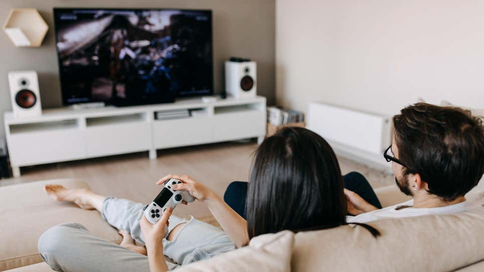 Photo of a couple playing Xbox