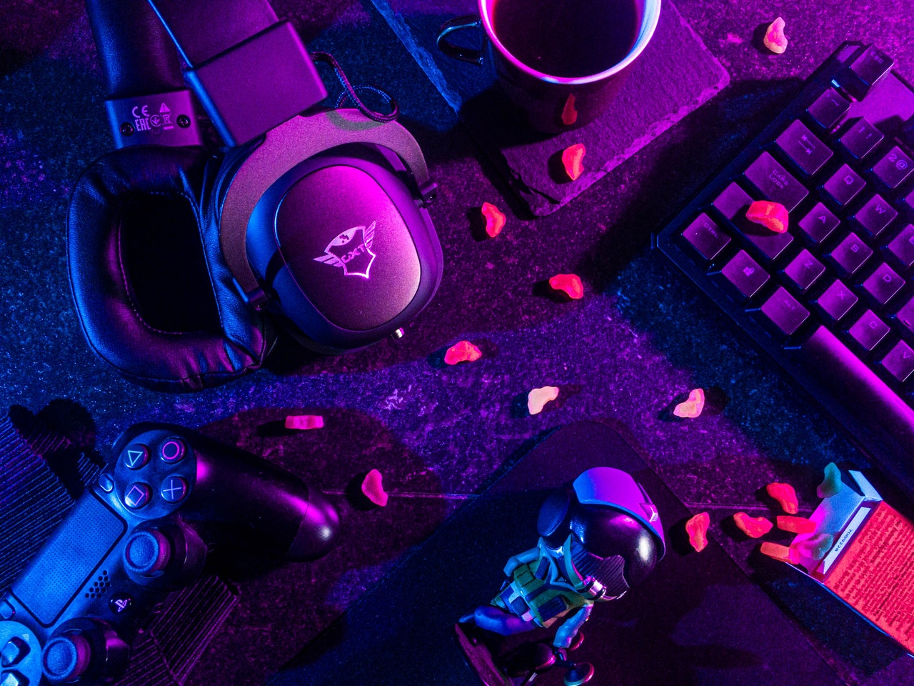 A photograph of a PlayStation controller,  headphones, keyboard, mug of coffee and snacks